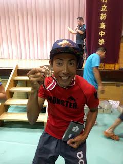 優勝メダルと盾を手にする篠崎プロ