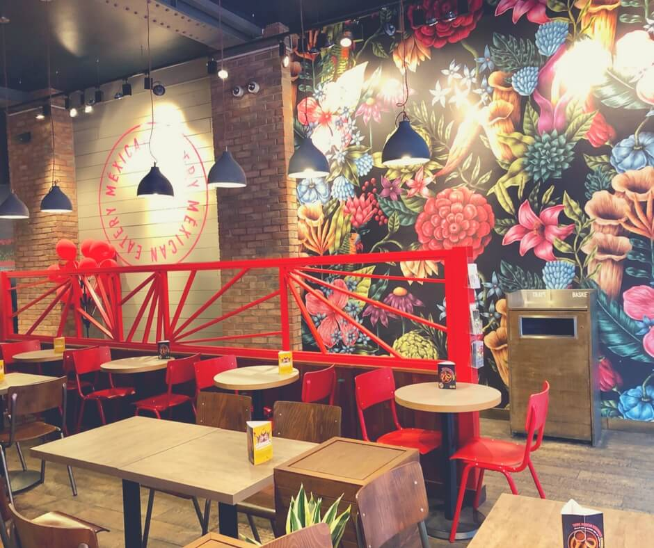 Inside the mexican eatery Barburriton, Nottingham. There's a colourful wall filled with blues, oranges, and red flowers.