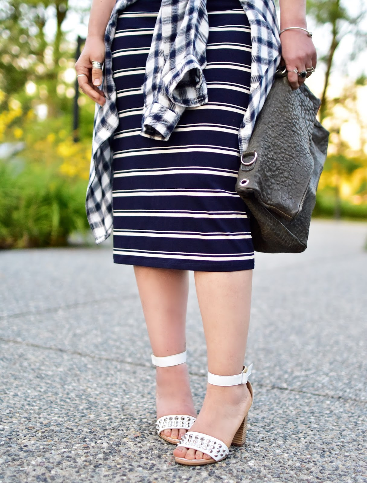 striped t-shirt dress, waist-tied plaid shirt, ankle-strap sandals, pebbled leather satchel