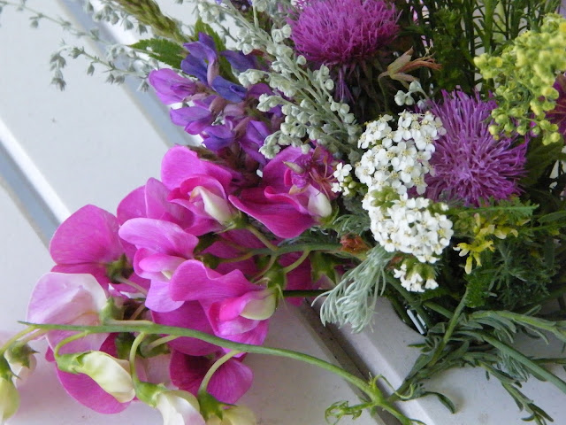 Bouquet of sweet peas, artemisia, and wildflowers.
