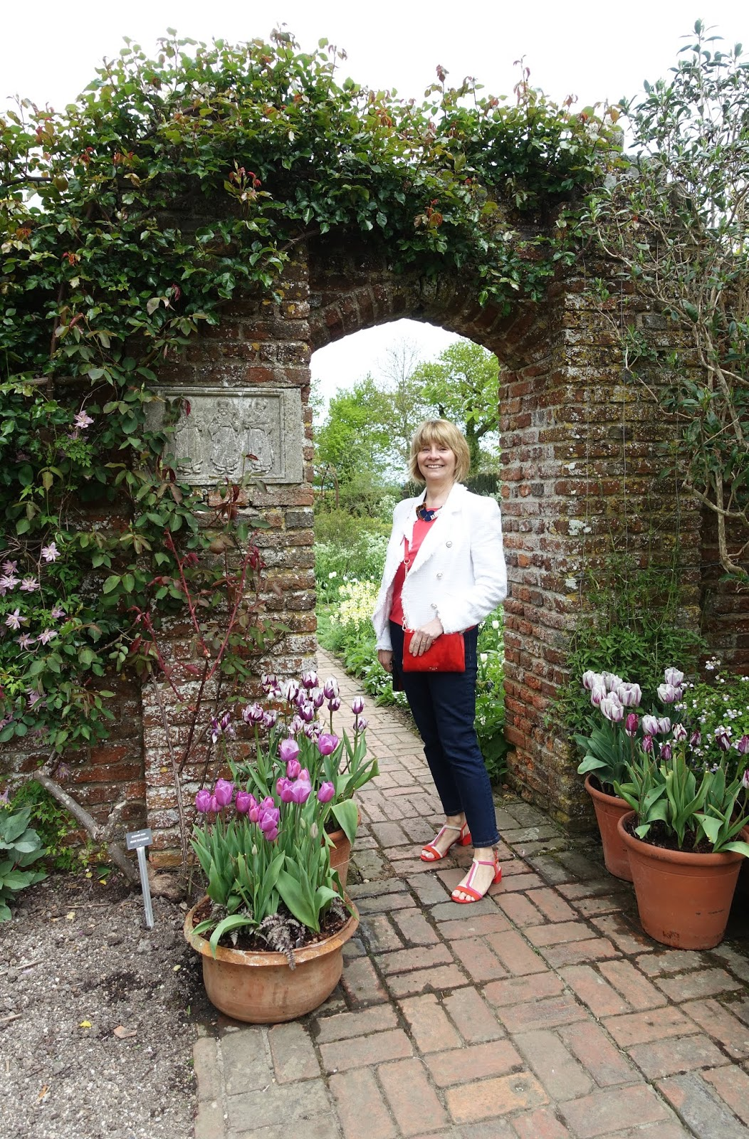 Woman posed by an arch with spring planting at Sissinghurst Castle Garden in Kent