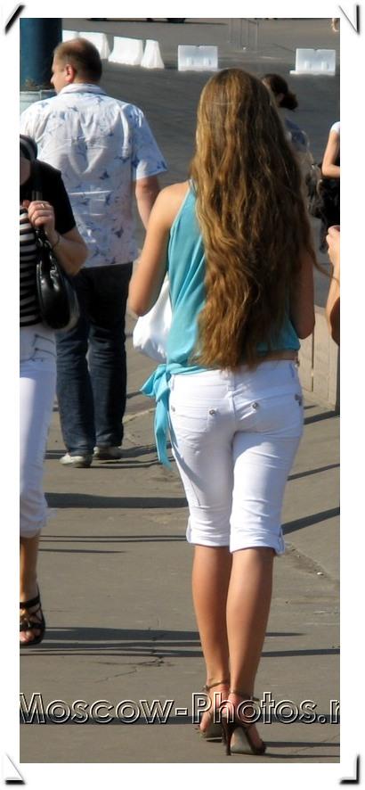 Slim long-haired girl in white jean breeches
