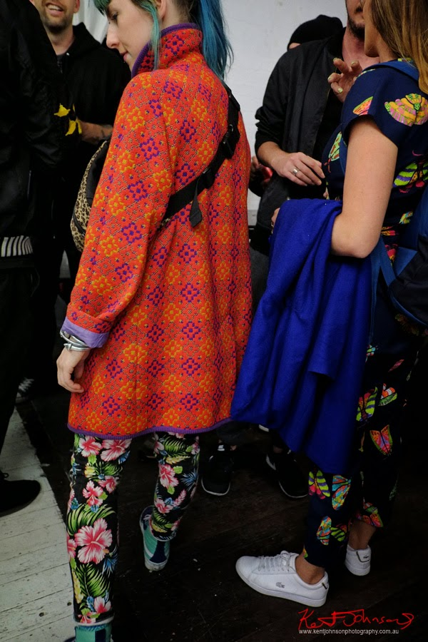Blue hair, orange and purple woven geometric pattern winter coat over floral print pants.