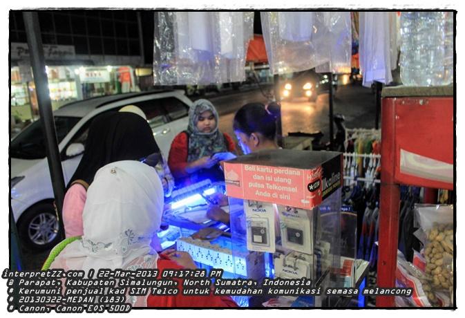 Gambar para pelancong mengerumuni penjual kad SIM telefon bimbit di Parapat, Kabupaten Simalungun, North Sumatra, Indonesia. Barang yang popular selain kad SIM ialah kepala plug adapter tu kerana tak sama seperti yang di Malaysia. # Teks: beli kartu perdana dan isi ulang pulsa Telkomsel anda di sini * Nokia # Friday, 22 March 2013, 21:17 # 20130322-medan (183).JPG # Canon Canon EOS 500D #