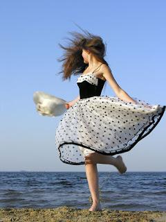 Γυναίκα με φόρεμα στην παραλία. Ακολουθεί το κείμενο: Τι είναι για μένα το στόμα σου; Μια κούπα λυπημένο λιβάνι, ένα δέντρο με φύλλο που κόβουν, έν' ανυπόφορο μεγάλο καράβι, μια φαρέτρα με βέλη υπέροχα.  Τι είναι για μένα το στήθος σου; Έν' άνθος μιας καινούργιας προσευχής μου, ένα ποίημα με φώτα που ποτέ δεν σβήνουν, ένα πηγάδι με πουλιά αλαζονικά και προπετή, ένα που δονείται ακόμα τανυσμένο τόξο.  Τι είναι για μένα το κορμί σου; Θέατρο είναι με ασάλευτη σιγή και άρμα με ταχύτητα κόκκινη· κι ακόμα είναι, ω, το δειλό, αβέβαιο βήμα κάτι πόθων που έχουν ασπρίσει τα μαλλιά τους.  Κυρία, θα σε αγγίξω με το νου μου. Θα σε αγγίξω και θα σε αγγίξω και θα σε αγγίξω ώσπου να μου δώσεις ξαφνικά ένα χαμόγελο, συνεσταλμένα άσεμνο (κυρία θα σε αγγίξω με το νου μου.) θα σε αγγίξω, αυτό είναι όλο, απαλά κι εσύ ολότελα θα γίνεις με απέραντη ευκολία το ποίημα που δεν θα γράψω όταν, το στόμα της που ξαφνικά ξυπνά, αρχίζει ολότελα με το δικό μου άγρια να παίζει (κι απ' τους μηρούς μου που ανασηκώνονται και ξεφυσούν μια δολοφονική βροχή φτάνει σκιρτώντας στο ανωφερές μοναδικό βαθύτατο λουλούδι που κουβαλά σε μια χειρονομία των γοφών της)