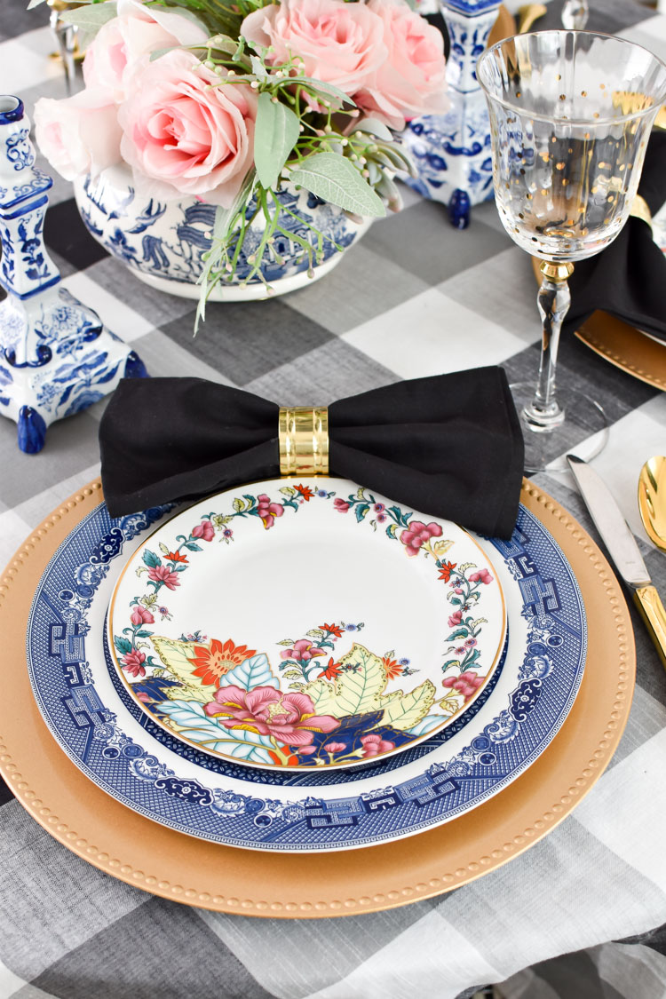 Bold and glam imperial leaf and tobacco leaf china paired with blue and white blue willow dinner plates and a floral centerpiece. Chinoiserie chic tablescape and centerpiece. #diningroom #diningroomdecor #chinoiserie #asiandecor #entertaining