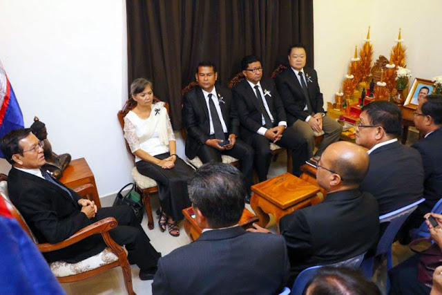 Kem Sokha (left) talks with CNRP members at the party's headquarters in Phnom Penh yesterday before they visited Wat Chas pagoda to pay their respects to Kem Ley. Photo supplied