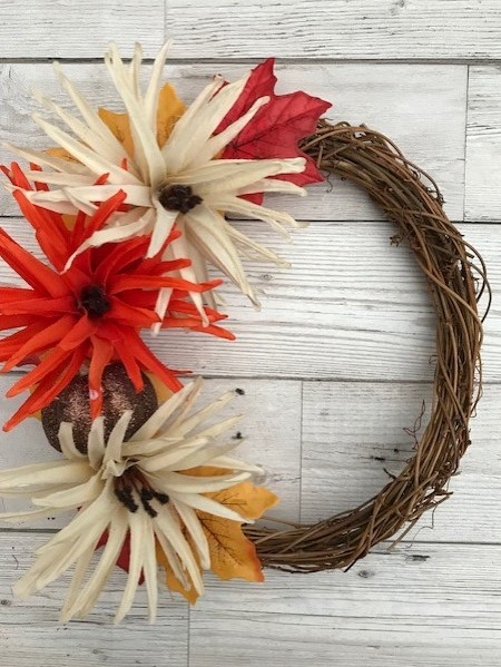 Wreath with a selection of red, biege, yellow and orange flowers and leaves along one side with a glittery pumpkin