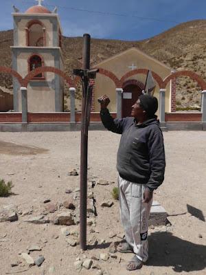 Der Katechet lädt mit dem Schlagen eines Steins auf ein Eisen in Ermangelung von Glocken zur Messe ein.