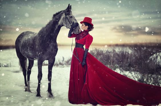 A woman dressed in Victorian or Neo-Victorian clothing (red skirt, jacket and hat) in the snow with a horse. women's neo-victorian fashion and clothing