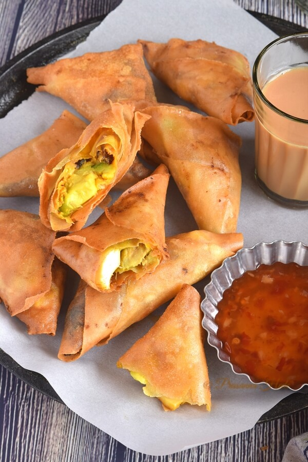 a black dish having avocado egg samosa roll along with Tea