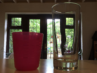 Pink ikea plastic glass on shelf next to a tall glass glass in front of patio windows