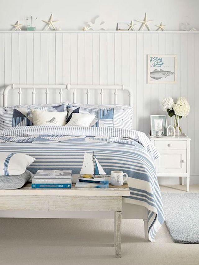 Dormitorio con friso de madera y repisa, decorado con motivos marineros
