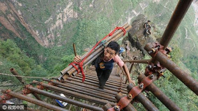 Villagers build ladder on cliff with steel pipes