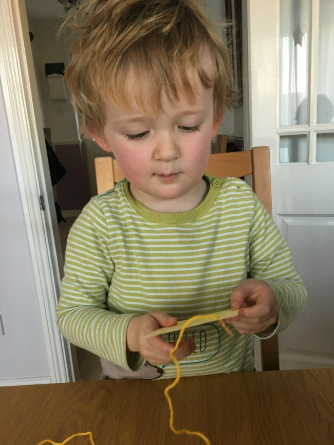 5-minute-games-for-toddlers-lacing-image-of toddler-threading-yarn-through-holes-in-card