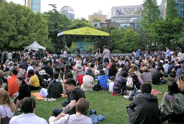 芝生に座って演奏をひたすら待つ観客と特設ステージ