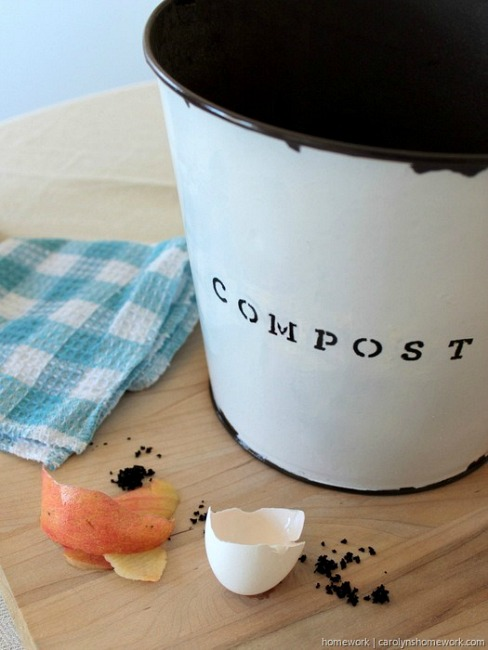 White painted galvanized bucket with the stenciled word compost on it, next to egg shells and peels and a blue checkered dish towel.