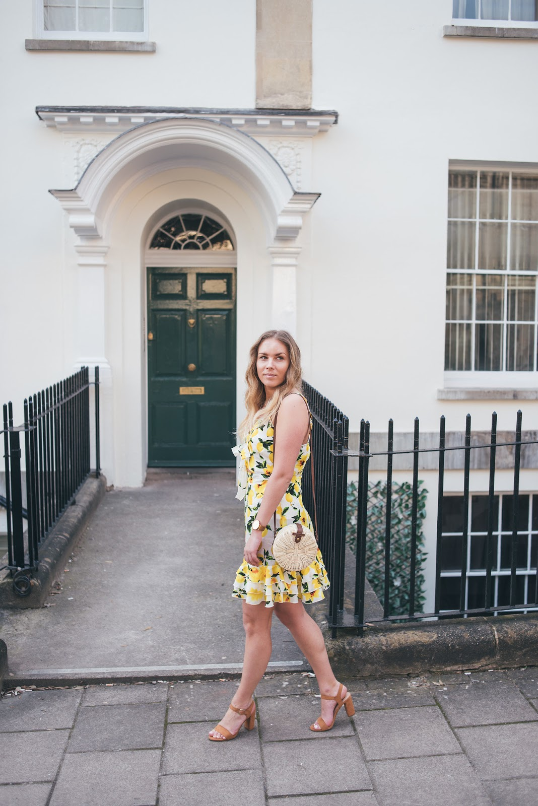 Rachel Emily in Lemon Print Dress in front of white houses with railings