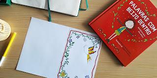 """Um postal com desenhos inspirados nos lenços dos namorados portugueses e o livro """"Palavras com beijo dentro"""""""