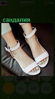 на женских ногах одеты сандалии светлого цвета
