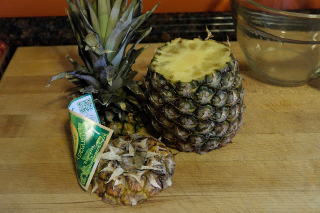 A whole pineapple, on a cutting board, with the top and bottom cut off.