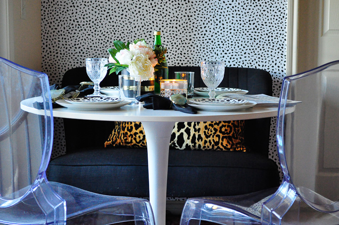 A boring and small 9x6 beige dining space in an apartment gets a glam makeover! No paint or power tools were needed, but the end result is gorgeous. Tanzania inspired spotted wallpaper, IKEA docksta table, bright pink rug and more. Love that starburst mirror!