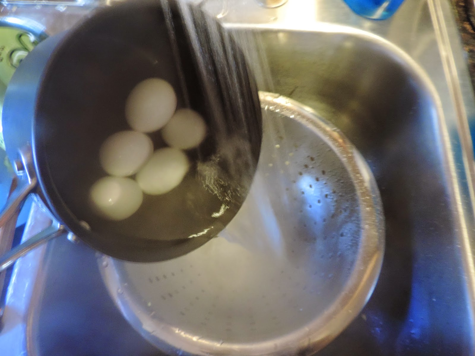 The eggs being poured into a strainer.