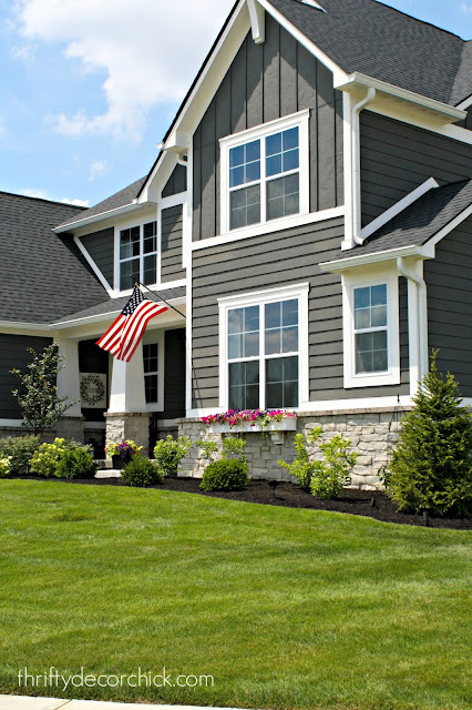Dark gray house with white trim, stone and columns