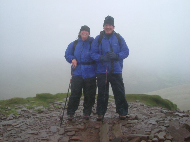 Essential-items-For-Walking-In-The-Mountains-In-South-Wales-man-and-woman-at-the-top-of-a-mountain-in-fog-and-rain