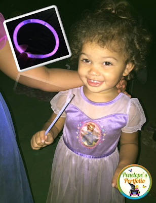 A little girl holding a glow in the dark necklace at night while camping