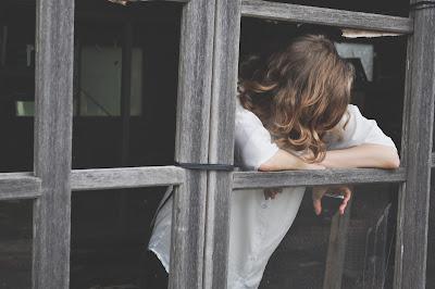 Mujer triste mirando la ventana en un día malo