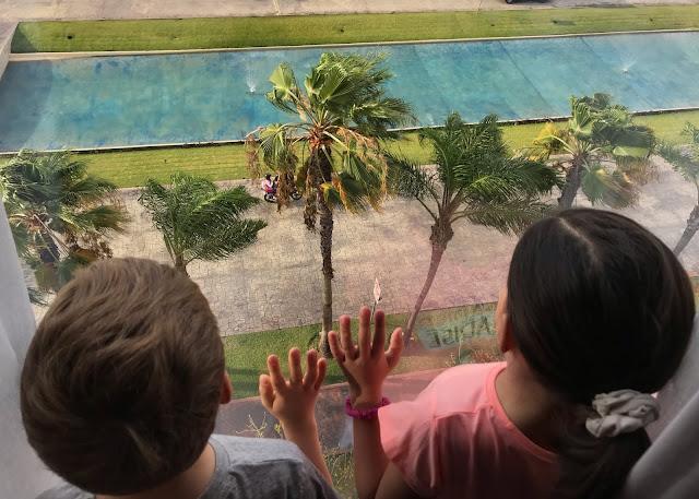 Dos niños vistos de espaldas asomados a una ventana