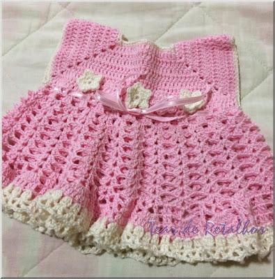Vestidinho de linha de algodão feito em crochê. Na cor rosa com arremates em branco.