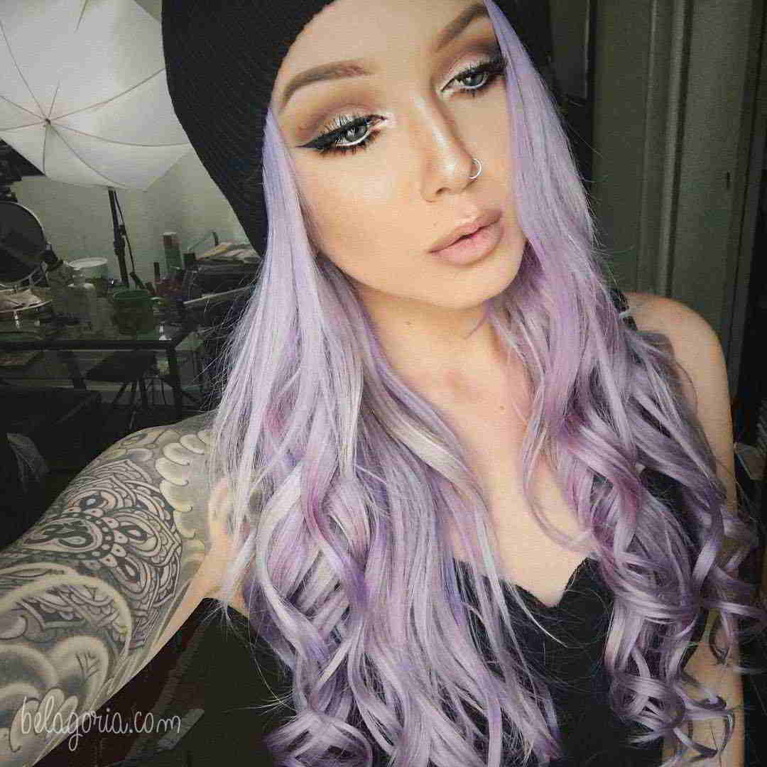 preciosa mujer de pelo lila con tatuajes espirituales femeninos
