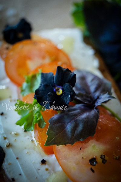 Frischkäse,Tomaten, Olivenöl auf die Stulle, dazu Kräuter wie dunkles Basilikum und Stiefmütterchen als essbare Blüte