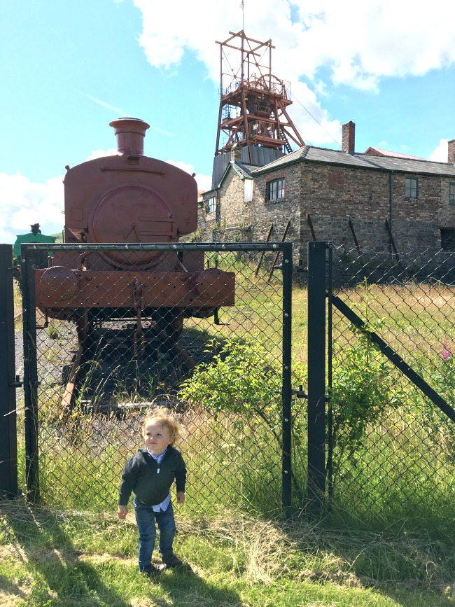 toddler-in-front-of-train-and-pit-wheel-at-big-pit-blaenavon