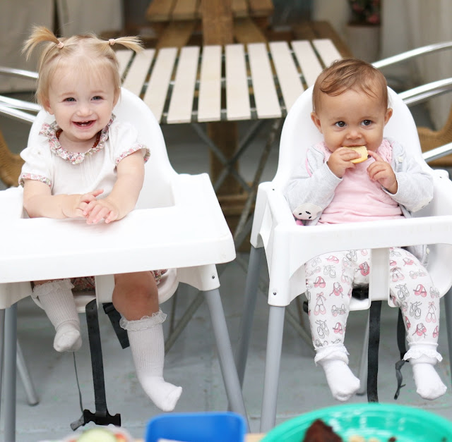 two babies sat in high chairs
