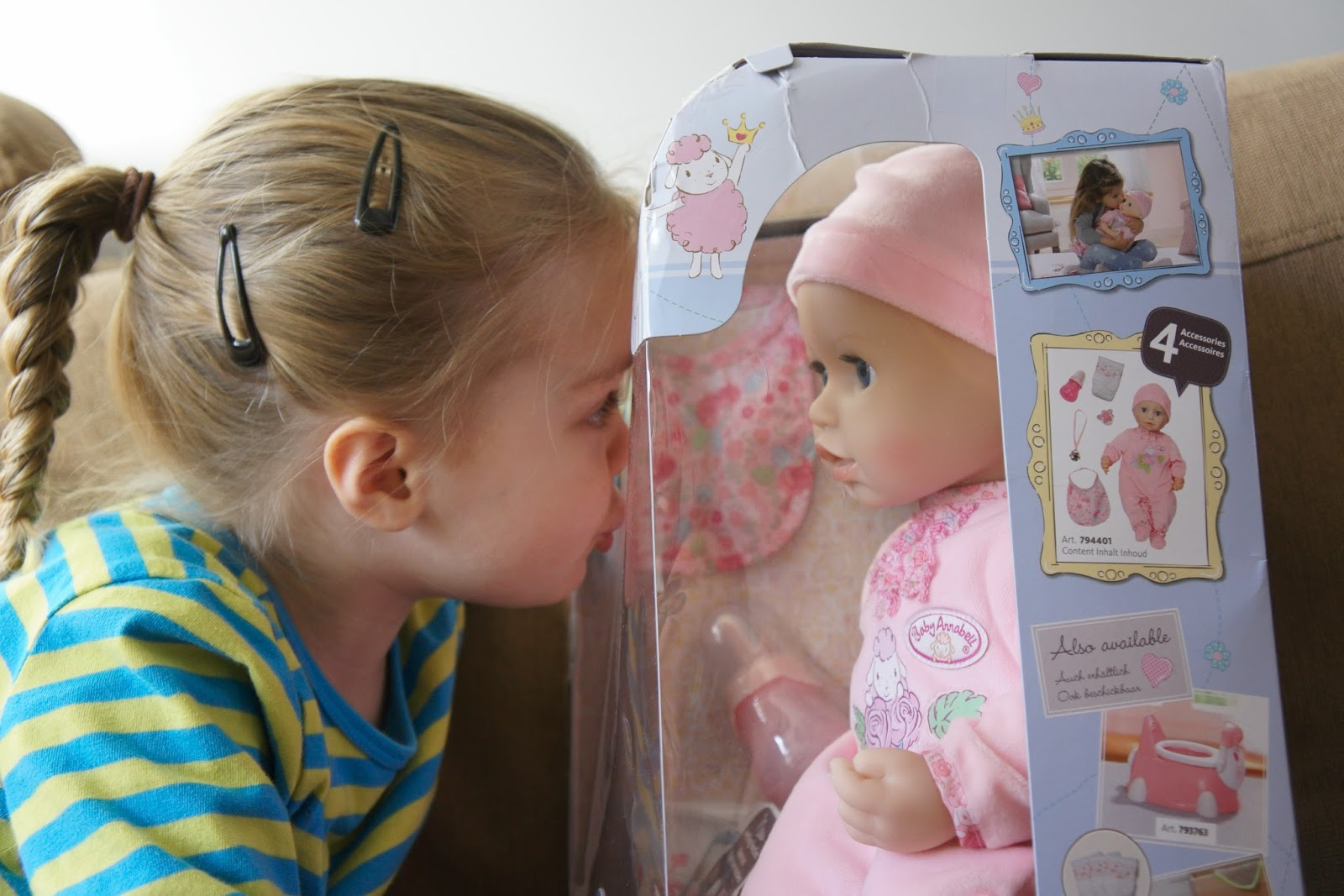 child looking at baby annabell doll in box