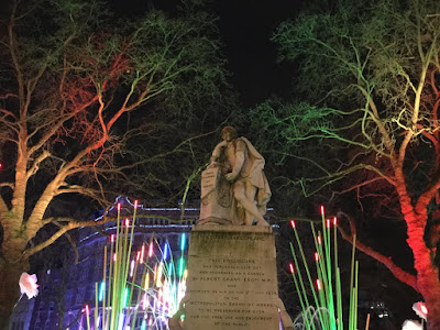 Pic of Shakespeare's statue surrounded by lit-up trees and plants of light