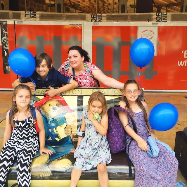 Mum and kids on Paddington Bench, blue balloons, kids, Paddington Bear, Paddington Station