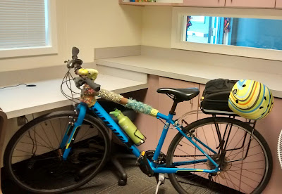 My blue Specialized Sirrus Sport bicycle with yellow and multi-striped bicycle helmet clipped to the trunkbag, parked in front of cupboards and counter-tops in an office-type setting