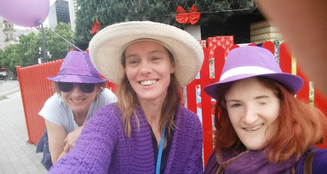 Three women wearing purple lined up in front of a red picket fence for a 'selfie' portrait. They are smiling.