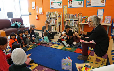 Storytime at Roseland library: presenter in a chair surrounded by children and a few parents sitting on a colorful carpet