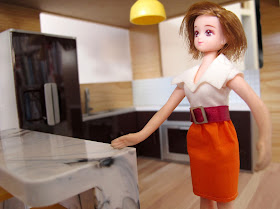 A doll standing in the kitchen of a Lori Loft to Love dolls' house.