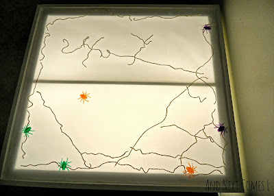 A giant spiderweb with colorful spiders on the light table from And Next Comes L