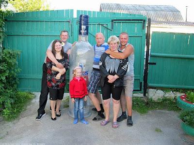 Lustige Familie posiert vor Kamera - Opa mit riesiger Wodka Flasche