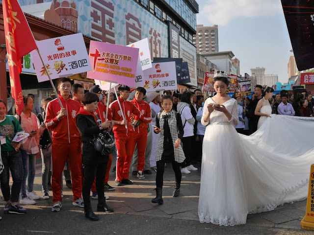 young woman wearing a bridal gown and using a mobile phone in Mudanjiang, China