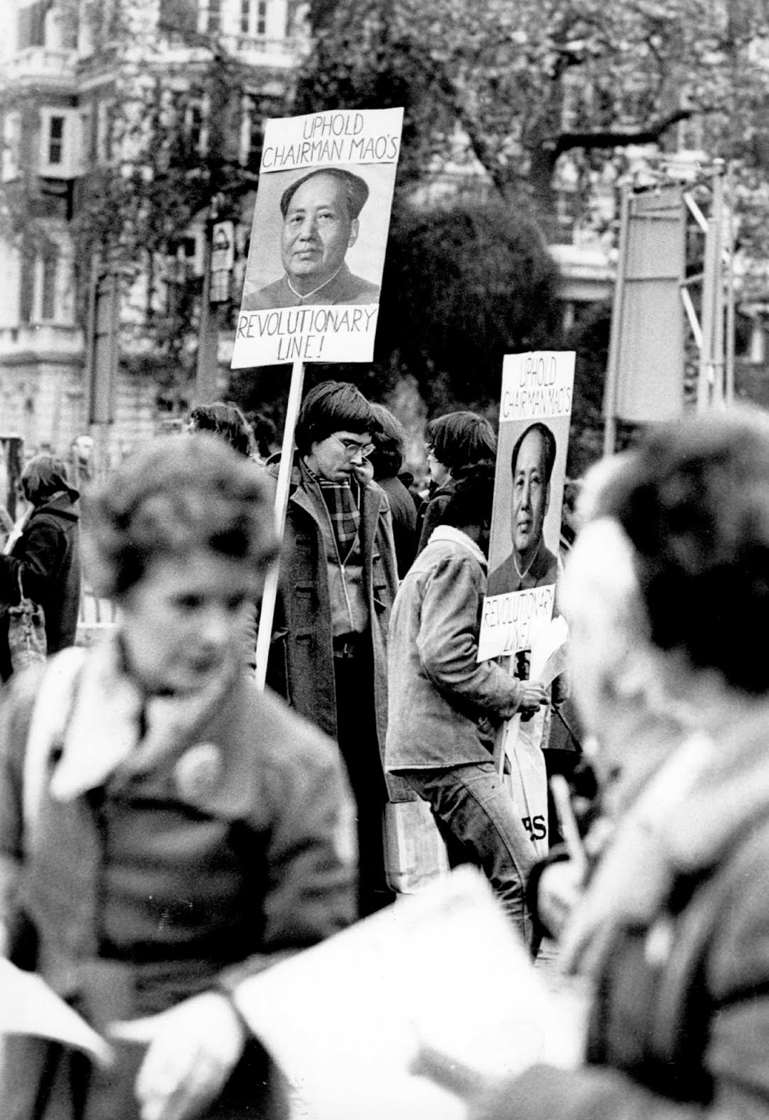 Demonstrators holding posters with pictures of Chairman Mao Tse Tung and the slogan 'Uphold Chairman Mao's Revolutionary Line'. 1976.