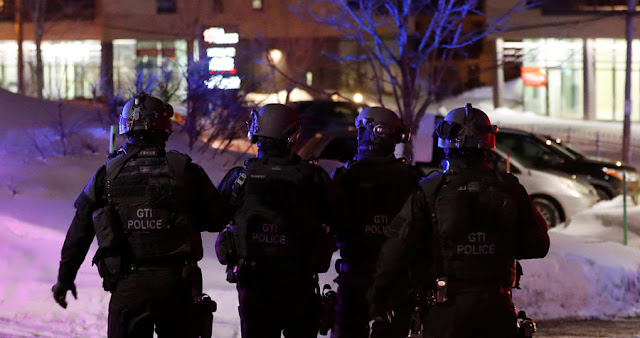 Image Attribute: SWAT team police officer walk around a mosque after a shooting in Quebec City, January 29, 2017. REUTERS/Mathieu Belanger