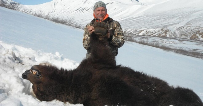 Man Poses Proudly With The Bear He Shot While It Was Hibernating. The Poor Animal Didn't Stand A Chance